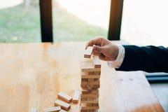 Hand van de stapelsspel van zakenman speelhoutsneden met de planning van strategie van projectleiding stock foto