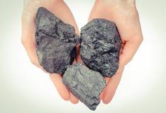 Hand van de steenkoolstukken, brandstof en macht van de vrouwenholding stock foto's