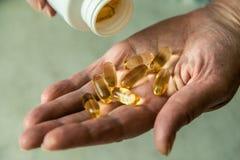 Hand van een bejaarde met pillen stock foto's
