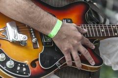 Hand van een gitarist die een gitaar houden royalty-vrije stock afbeeldingen