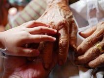 Hand van een klein babymeisje op handen van haar grootmoeder en moeder - familieband stock afbeeldingen