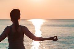 Hand van een meisje dat op de achtergrond van het overzeese close-up mediteert stock foto