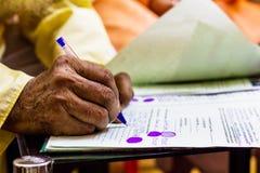 Hand van een oude mens die belangrijk wettelijk document schrijven stock foto's