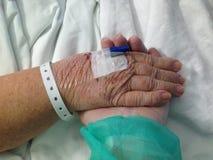 Hand van een oude vrouw in een het ziekenhuisbed royalty-vrije stock afbeeldingen