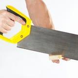 Hand van een timmerman die een houten blok met een handsaw snijden Stock Afbeeldingen