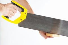Hand van een timmerman die een houten blok met een metaalzaag zagen Stock Foto