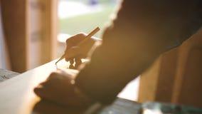 Hand van een timmerman die meting van een houten plank nemen de achtergrond van de zongloed ob stock video