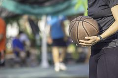 Hand van een vrouw die een horloge dragen en oud basketbal houden stock afbeelding