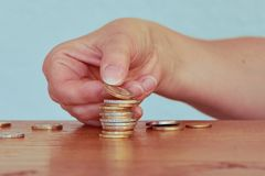 Hand van een vrouw met een stapel van één en twee Euro muntstukken Royalty-vrije Stock Foto's
