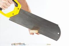 Hand van een werkman die een houten blok met een handsaw snijden Stock Foto