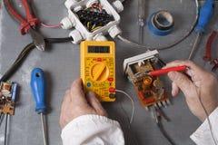Hand van elektricien met multimetersonde bij elektromechanismekabinet Techniekhulpmiddelen Royalty-vrije Stock Fotografie