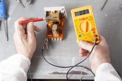 Hand van elektricien met multimetersonde bij elektromechanismekabinet Techniekhulpmiddelen Royalty-vrije Stock Foto