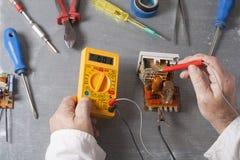 Hand van elektricien met multimetersonde bij elektromechanismekabinet Techniekhulpmiddelen Stock Afbeeldingen
