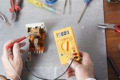 Hand van elektricien met multimetersonde bij elektromechanismekabinet Techniekhulpmiddelen Stock Foto