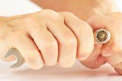 Hand van hersteller met een moersleutel om noot dichte omhooggaand aan te halen royalty-vrije stock afbeeldingen