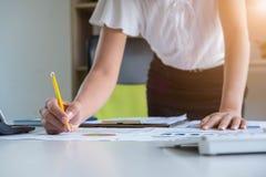 Hand van het gele potlood van de vrouwenvangst, Vrouw die aan bureau, oranje lichte gloed werken royalty-vrije stock fotografie