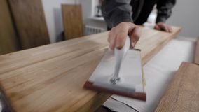 Hand van het instrument van de mensenholding en oppoetsend licht houten paneel stock footage