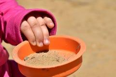 Hand van 3 jaar oude plastic pattypan van de meisjesholding met zand Royalty-vrije Stock Fotografie