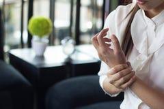 Hand van jonge vrouwen die is er pijn in de handen door gebruikscom worden veroorzaakt stock fotografie