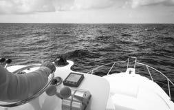 Hand van kapitein op stuurwiel van motorboot in de blauwe oceaan tijdens de visserijdag Succes visserijconcept Oceaanjacht stock foto's