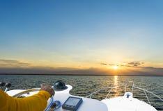 Hand van kapitein op stuurwiel van motorboot in de blauwe oceaan tijdens de visserijdag Succes visserijconcept Oceaanjacht royalty-vrije stock afbeeldingen