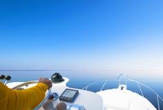 Hand van kapitein op stuurwiel van motorboot in de blauwe oceaan tijdens de visserijdag Succes visserijconcept Oceaanjacht stock foto