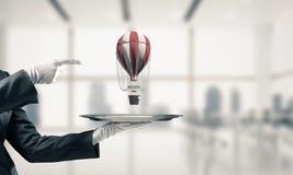 Hand van kelner die ballon op dienblad voorstellen Stock Foto