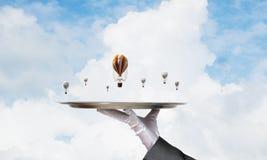 Hand van kelner die ballons op dienblad voorstellen Stock Foto's