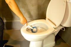Hand van kom die van het vrouwen de schoonmakende toilet blauwe borstel gebruiken royalty-vrije stock afbeeldingen