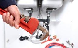 Hand van loodgieter met moersleutel Stock Foto