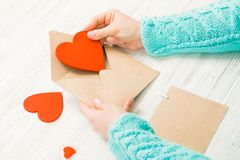 Hand van meisje het schrijven liefdebrief op de Valentijnskaartendag van Heilige Handma Stock Foto