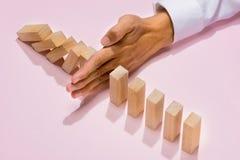 Hand van omvergeworpen de domino's ononderbroken van het zakenmaneinde Stock Afbeeldingen