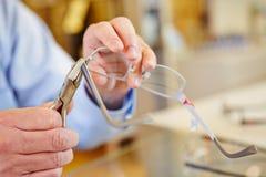 Hand van opticien het bevestigen glazen Royalty-vrije Stock Foto