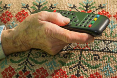 Hand van oude vrouw met TV-bestuurder Stock Afbeeldingen