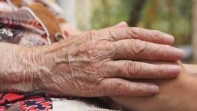 Hand van oude vrouwen die jonge vrouwelijke wapens strijken openlucht Kleindochter en grootmoeder het besteden tijd samen buiten stock video