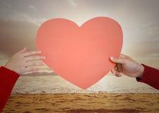 Hand van paar die rood hart op strand houden Royalty-vrije Stock Foto