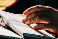 Hand van priester op de Bijbel stock afbeeldingen