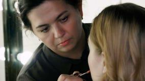 Hand van samenstellingsmeester, het schilderen lippen van jong mooi model Lopende make-up stock video