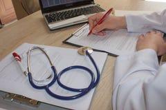 Hand van specialist op een voorschrift Vrouwelijke medische arts die iets schrijven die op haar kantoor zitten Stock Afbeelding
