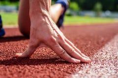 Hand van sportman op positie van het renbaan de lage begin Agent klaar dicht te stijgen De flexibiliteit is capaciteit zich uit t royalty-vrije stock foto's