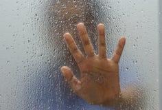 Hand van vreemdeling op berijpt glas met waterdaling royalty-vrije stock fotografie