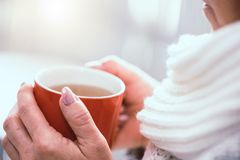 Hand van vrouw die een mok hete thee houdt stock afbeeldingen