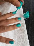 hand van vrouw die haar spijkers in aquamarijnkleur schilderen stock fotografie