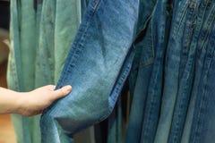 Hand van vrouw die jeans in de opslag kiezen Selectieve nadruk royalty-vrije stock afbeeldingen