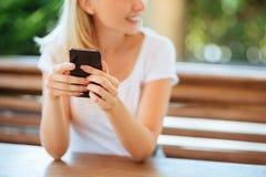 Hand van vrouw die smartphone op houten lijst gebruiken royalty-vrije stock afbeeldingen