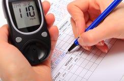 Hand van vrouw het schrijven gegevens van glucometer aan medische vorm Stock Foto's