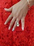 hand van vrouw met toebehoren wat betreft haar buik in een rode kleding royalty-vrije stock fotografie