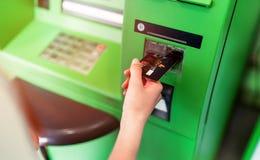 Hand van vrouwen met een creditcard, die ATM gebruiken Vrouw die een ATM-machine met zijn creditcard met behulp van Royalty-vrije Stock Foto