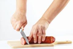 Hand van vrouwen met een mes sneed gerookte worst royalty-vrije stock foto