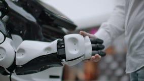 Hand van zakenman het schudden handen met een Android-robot Het concept menselijke interactie met kunstmatige intelligentie stock videobeelden